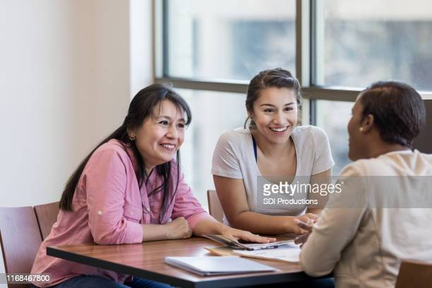 Mom and daughter talk with loan officer