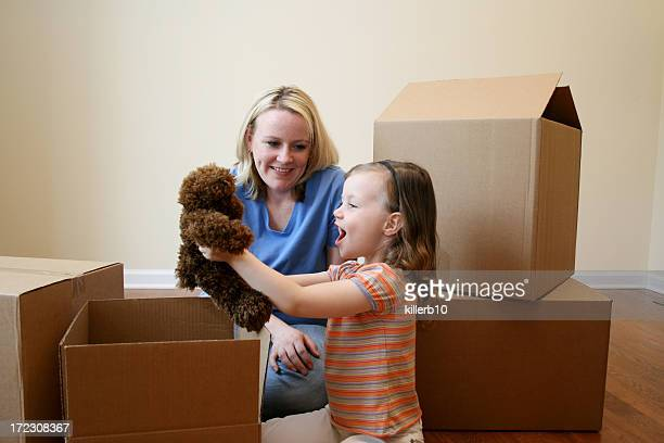 Mom and daughter unpacking toy in new house