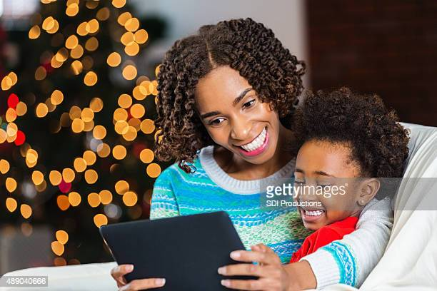 Mom and daughter using tablet to video chat on Christmas
