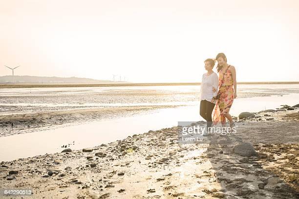 Mom and daughter walking by seashore