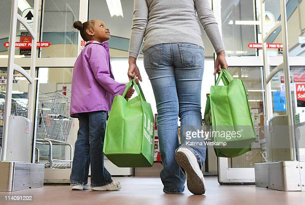 Mom and daughter walking out of grocery store.