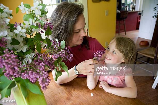 Mutter und Tochter mit Blumen im kitchen table