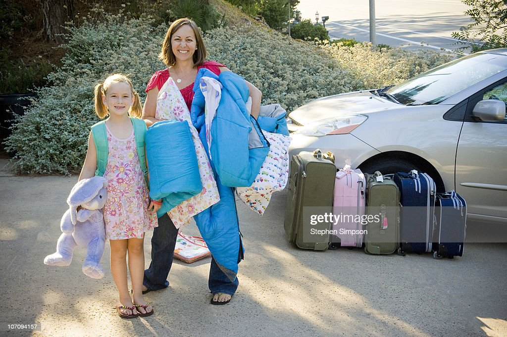 Mom and girl packing the van for a drive vacation : Stock Photo