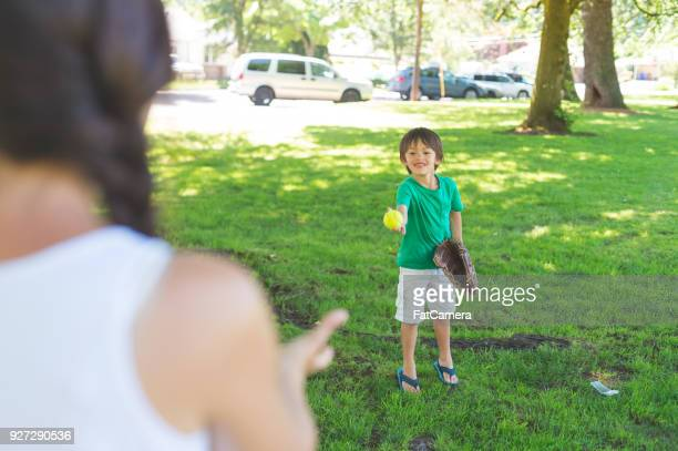 mom and her boy play catch at the park - baseball mom stock pictures, royalty-free photos & images