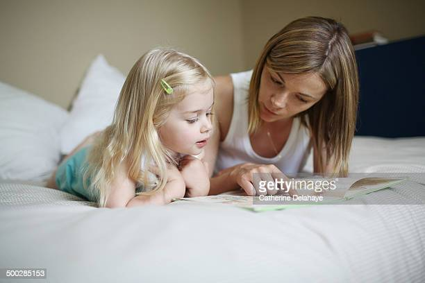a mom and her daughter reading a book - family with one child stock pictures, royalty-free photos & images