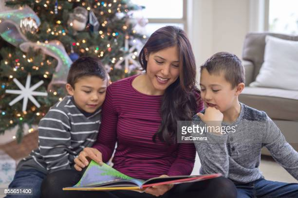 A mom and her two sons read a Christmas book together in front of the decorated tree