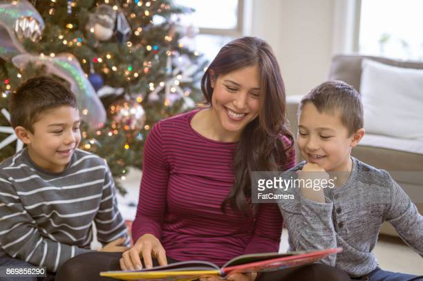 a mom and her two sons read a christmas book together in front of the decorated tree - shock tactics stock pictures, royalty-free photos & images