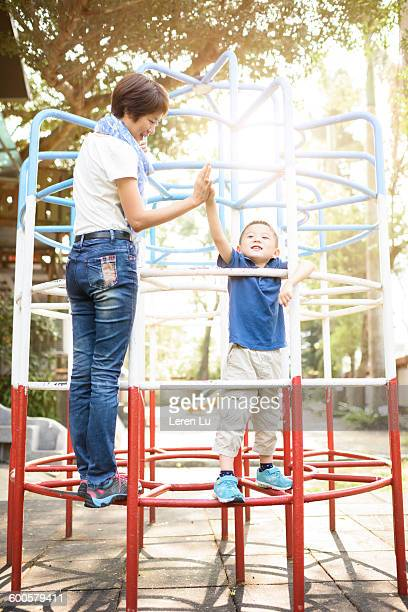 Mom and kid clasping hands on jungle gym
