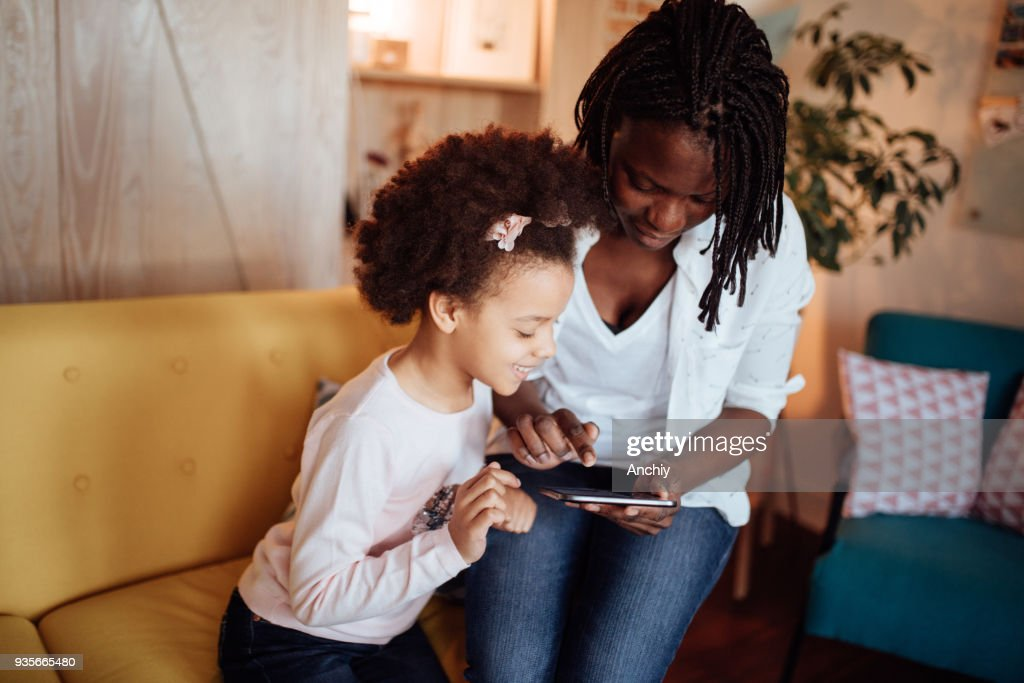 Mom and kids playing games on digital tablet : Stock Photo