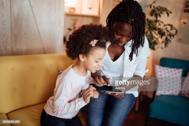Mom and kids playing games on digital tablet