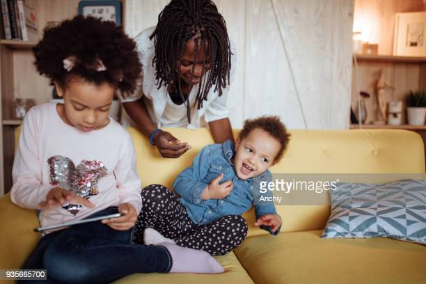 mom and kids playing games on digital tablet - interracial cartoon stock photos and pictures