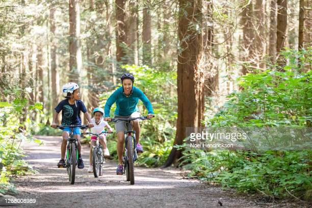 mom and kids race on bikes - sports equipment stock pictures, royalty-free photos & images