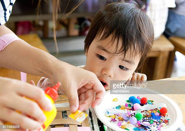 mom and little girl are making ornaments. - mamigibbs stock photos and pictures