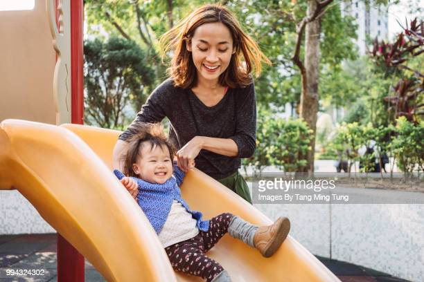 mom and lovely baby playing slide in playground joyfully. - spielgerät stock-fotos und bilder