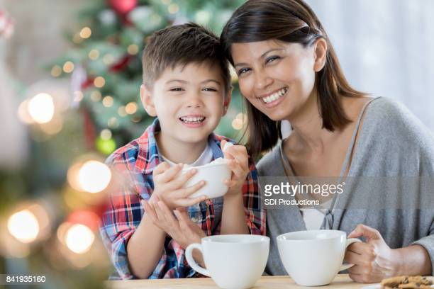 mom and son enjoy cocoa on christmas eve - filipino christmas family stock pictures, royalty-free photos & images