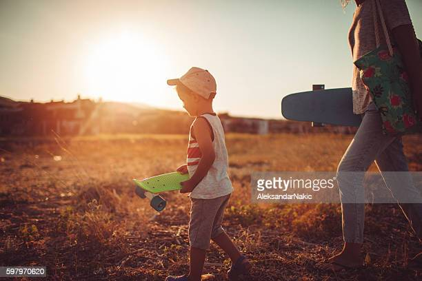 mom and son getting ready for skateboarding - mothers day beach stock pictures, royalty-free photos & images