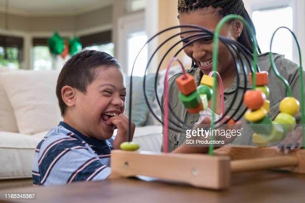 mom and son laugh together while playing in living room - down syndrome stock pictures, royalty-free photos & images