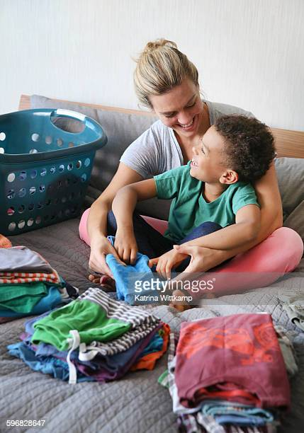 Mom and son laugh while folding laundry
