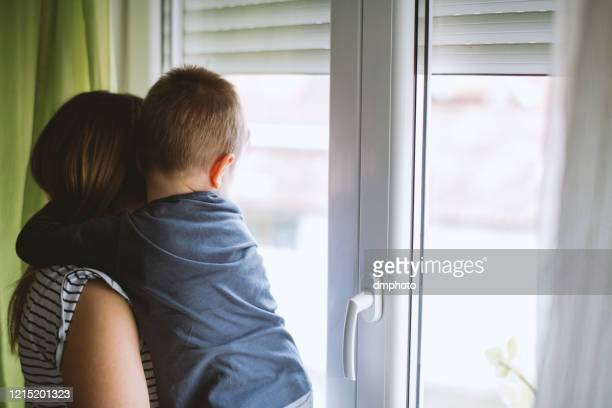 mom and son looking through window at home - son stock pictures, royalty-free photos & images