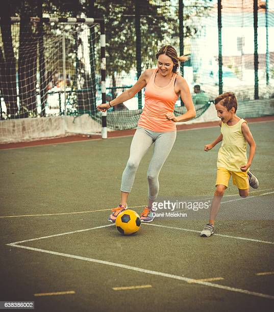 Mom and son playing football on stadium