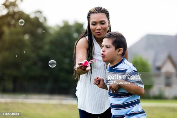 mom and son playing with bubble wand - down syndrome stock pictures, royalty-free photos & images