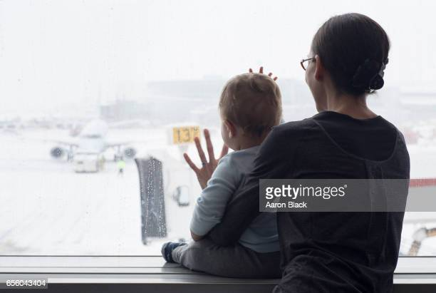 Mom and son quiet moment looking at airplanes in the snow.