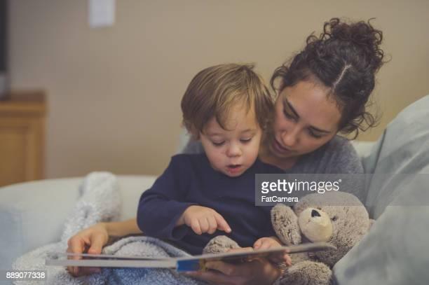 mamá e hijo lectura libro juntos en sala de estar - leer fotografías e imágenes de stock