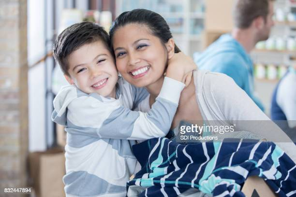 mom and son receive box of clothing during clothing drive - homeless shelter stock pictures, royalty-free photos & images