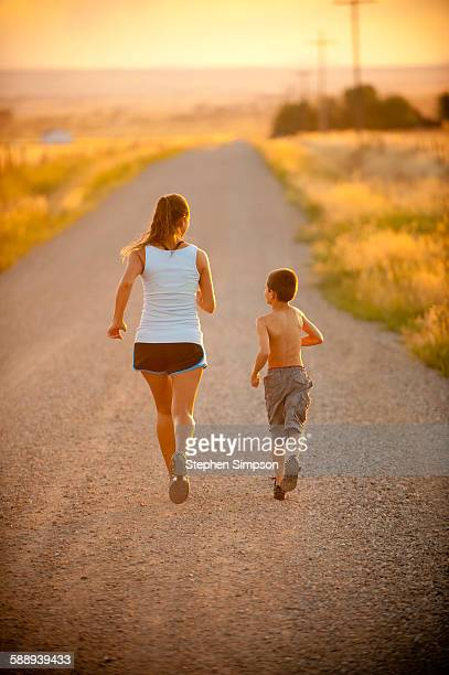 mom and son running together, country road