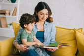 Mom and son sitting on yellow sofa and reading book