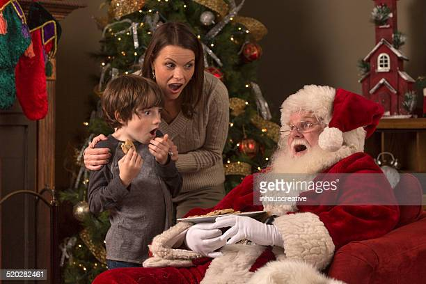 Mom and son sneaking up on sleeping Santa