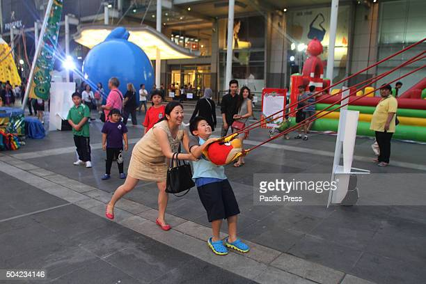 Mom and son take part in an activity of a real life Angry birds game during National Children's Day at the front of Central World The shopping mall...