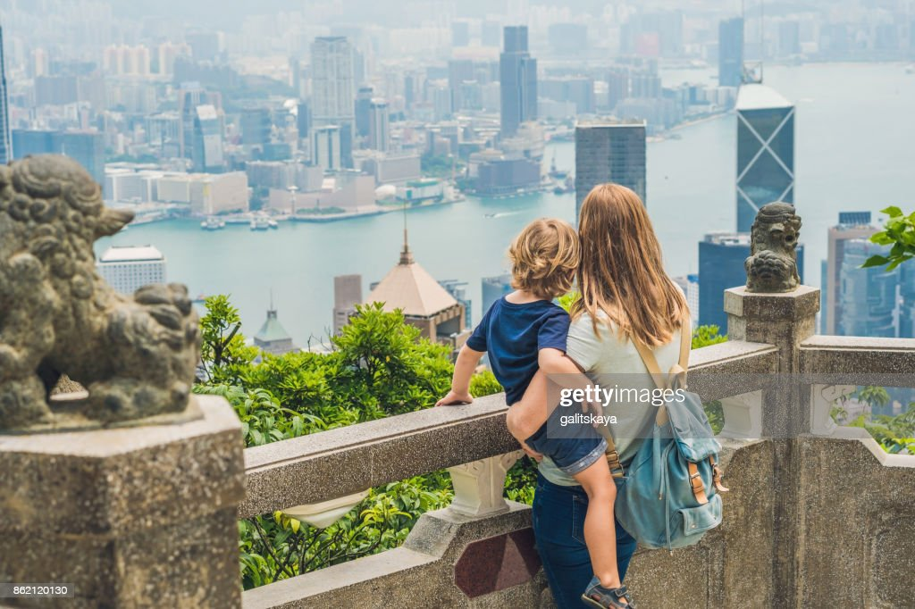 Mom and son travelers at the peak of Victoria against the backdrop of Hong Kong. Traveling with children concept : Stock Photo
