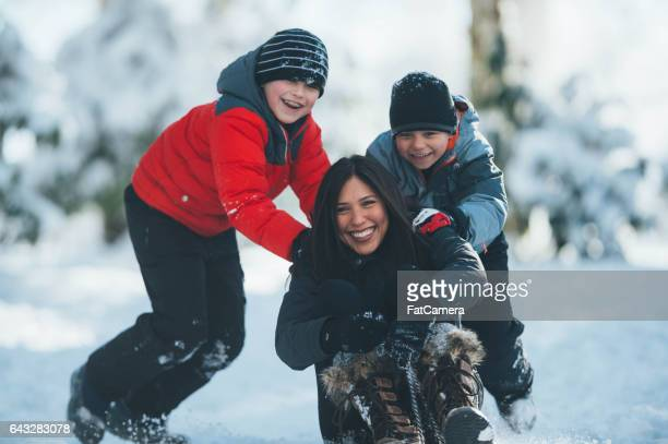 Mom and sons playing in snow