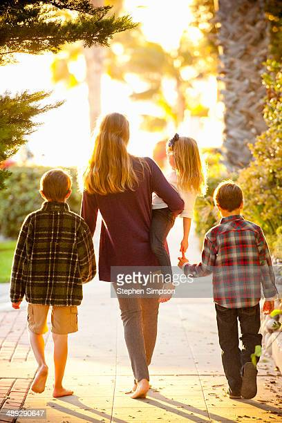 mom and three kids going for a barefoot walk