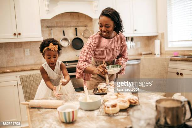 mom and toddler baking together - african american family home stock photos and pictures