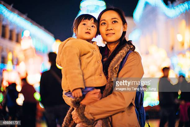 Mom and toddler girl looking at Christmas lights