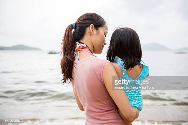 Mom and toddler girl talking on the beach