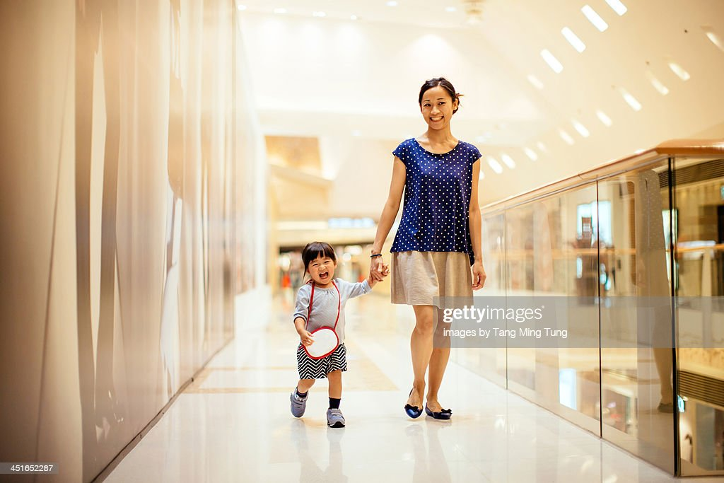 Mom and toddler girl walking in shopping mall : Stock Photo