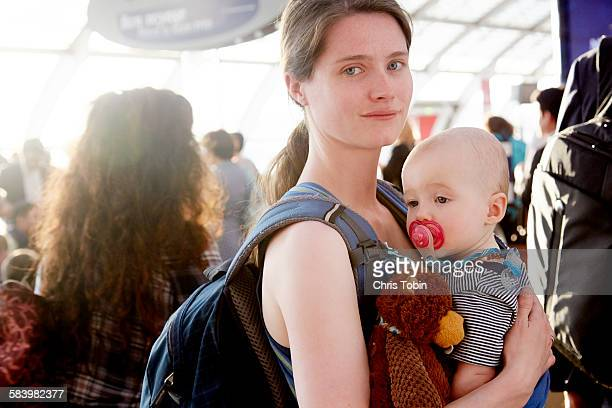 mom and toddler in busy airport - mama bear stock photos and pictures