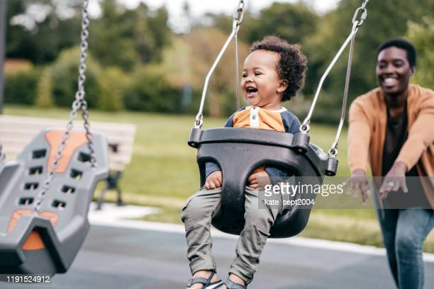 mom and toddler in the playground - swinging stock pictures, royalty-free photos & images