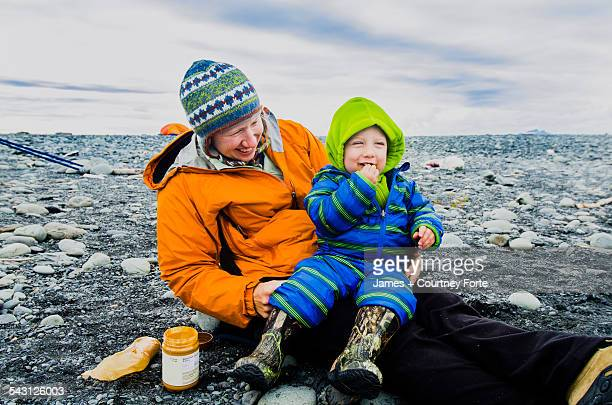 Mom and two year old son enjoy a peanut butter and cracker snack on the rocky beach next to Bear Lake in Kenai Fjords National Park, Alaska.