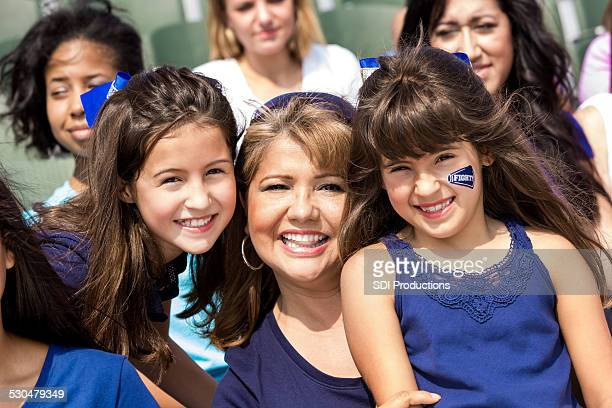 Mom and young daughters cheering for favorite football team