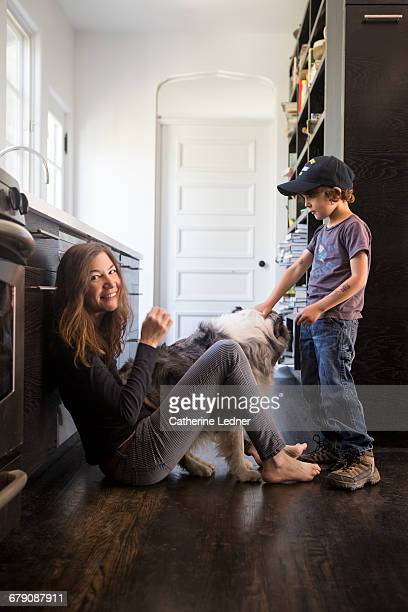 Mom and young son with dog in kitchen