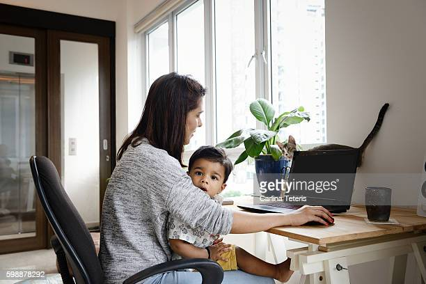 Mom and young son working on a laptop with a cat on the desk