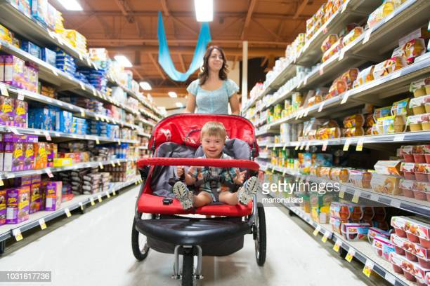 mom at the grocery store with his son with down syndrome - disabilitycollection stock pictures, royalty-free photos & images