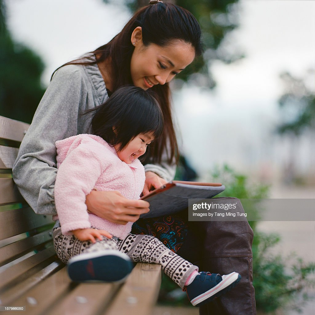 Mom & Baby playing with tablet in a park joyfully : Stockfoto