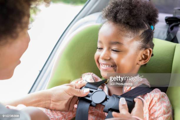 Mom buckles adorable little girl into car seat