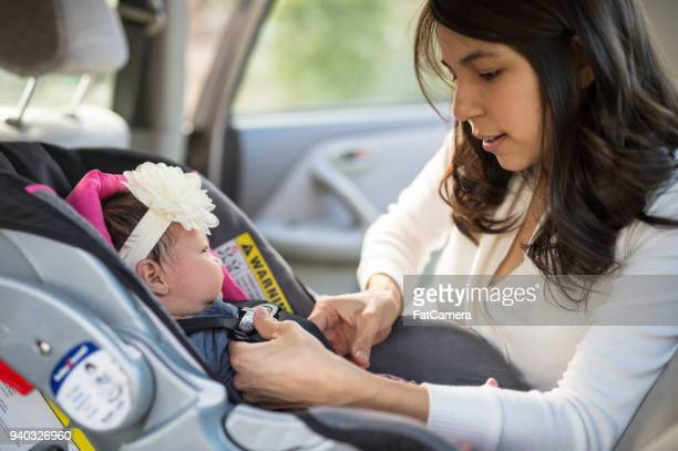 Mom Buckling Infant Into Car Seat