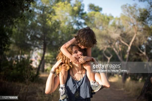 mom carrying baby boy on her shoulders - wachsamkeit stock-fotos und bilder